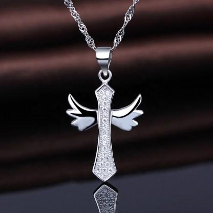 Croix Angel en argent brillant 925 avec zircons transparents by White Alpina. Ce collier Croix Angel est livré dans un écrin et une chaîne.