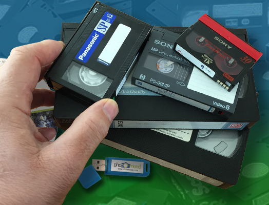Hand holding VHS and analog video tapes