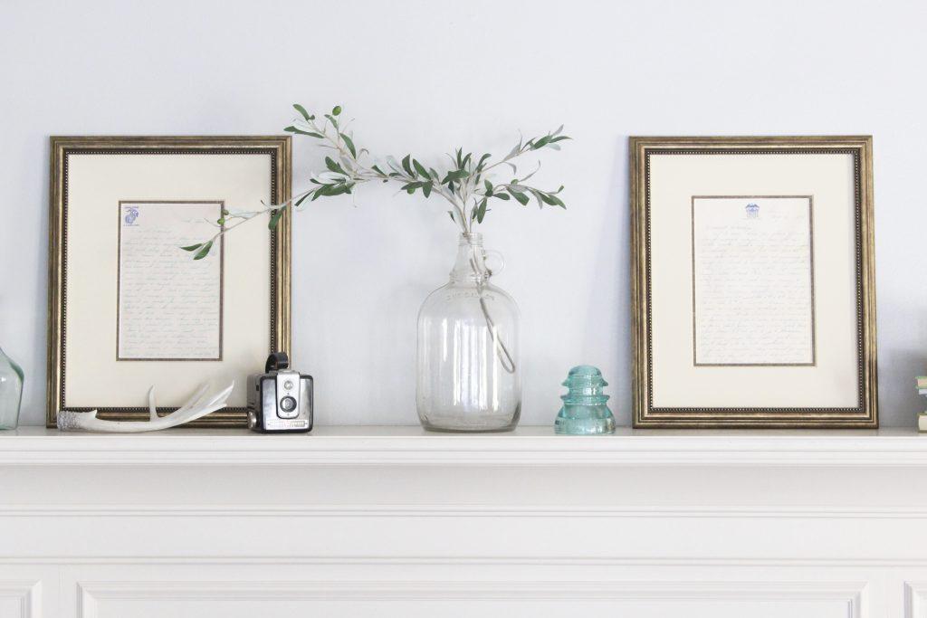 spring mantel-bottles- insulators- vintage cameras- mantel decor- decorating a mantel for spring- mantles- keepsakes- how to use keepsakes in decor