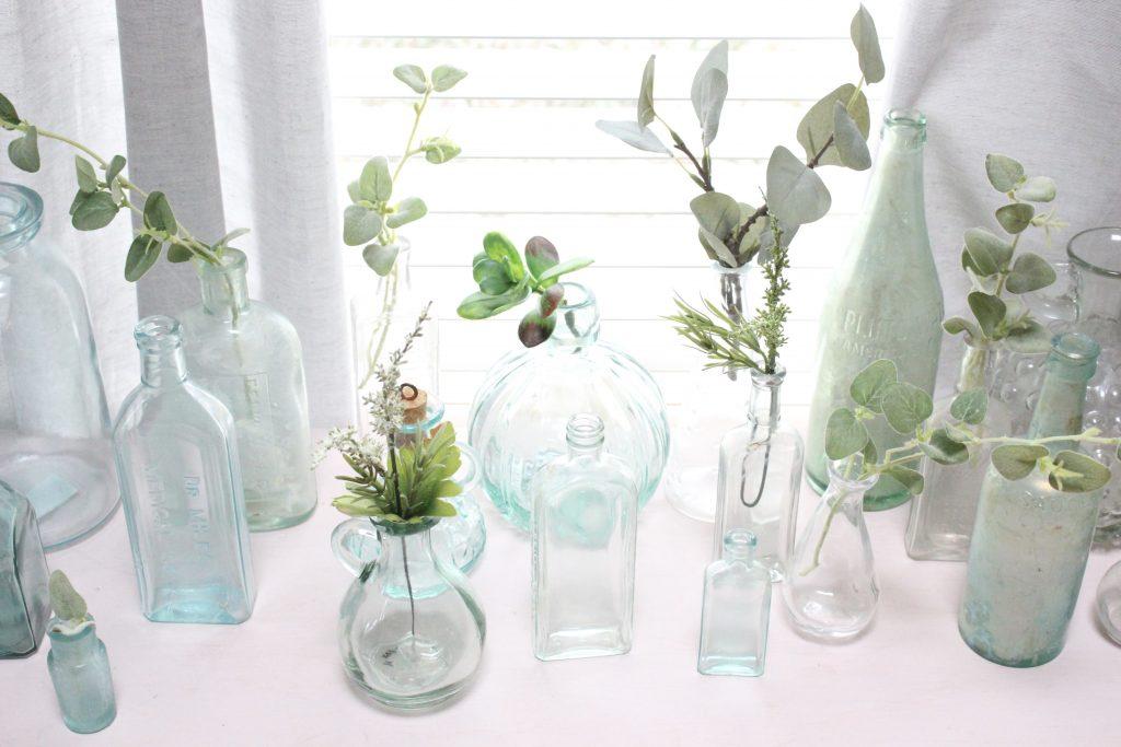 vintage bottles on display- vintage finds- green bottles- old bottles- jars- vases- displaying bottles- thrift store finds- antique bottles
