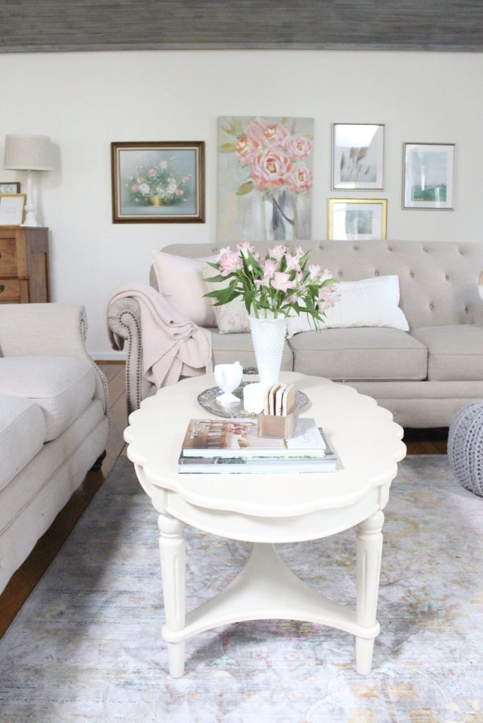 An updated family room space with seasonal spring decor, spring- family room decor- gray washed ceiling- pink decor- gray decor- using pastels in decorating- large family room space- French country coffee table- tufted couch