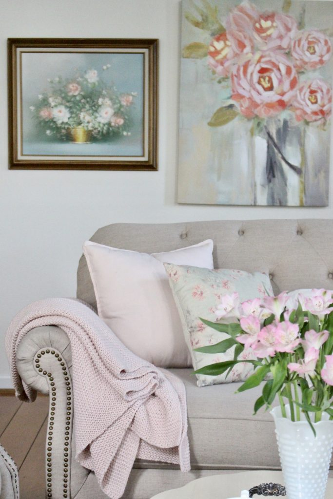 An updated family room space with seasonal spring decor, spring- family room decor- gray washed ceiling- pink decor- gray decor- using pastels in decorating- large family room space- vintage wall art