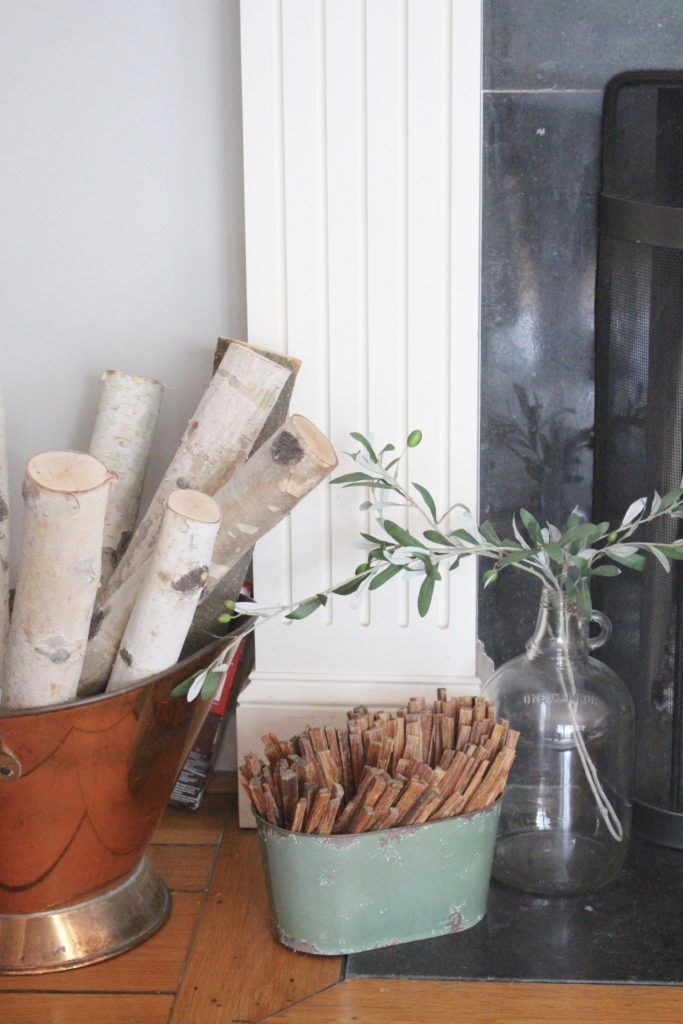 Transitional Fall Mantel- how to decorate the easy way for fall- mantel decor- mantles- decorating a fall mantel- autumn decor- decorating with wheat- pumpkins- olive branches- glass jug- copper firewood bin