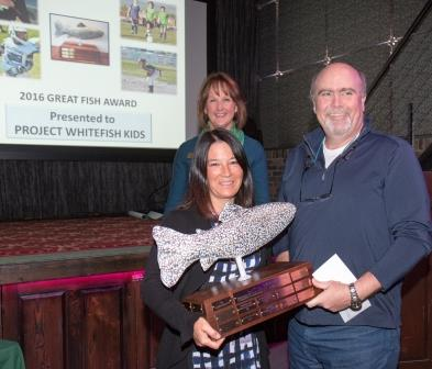 Lynnette Donaldson and Cliff Hayden of Project Whitefish Kids accept the Great Fish Award from Ardy Whisler