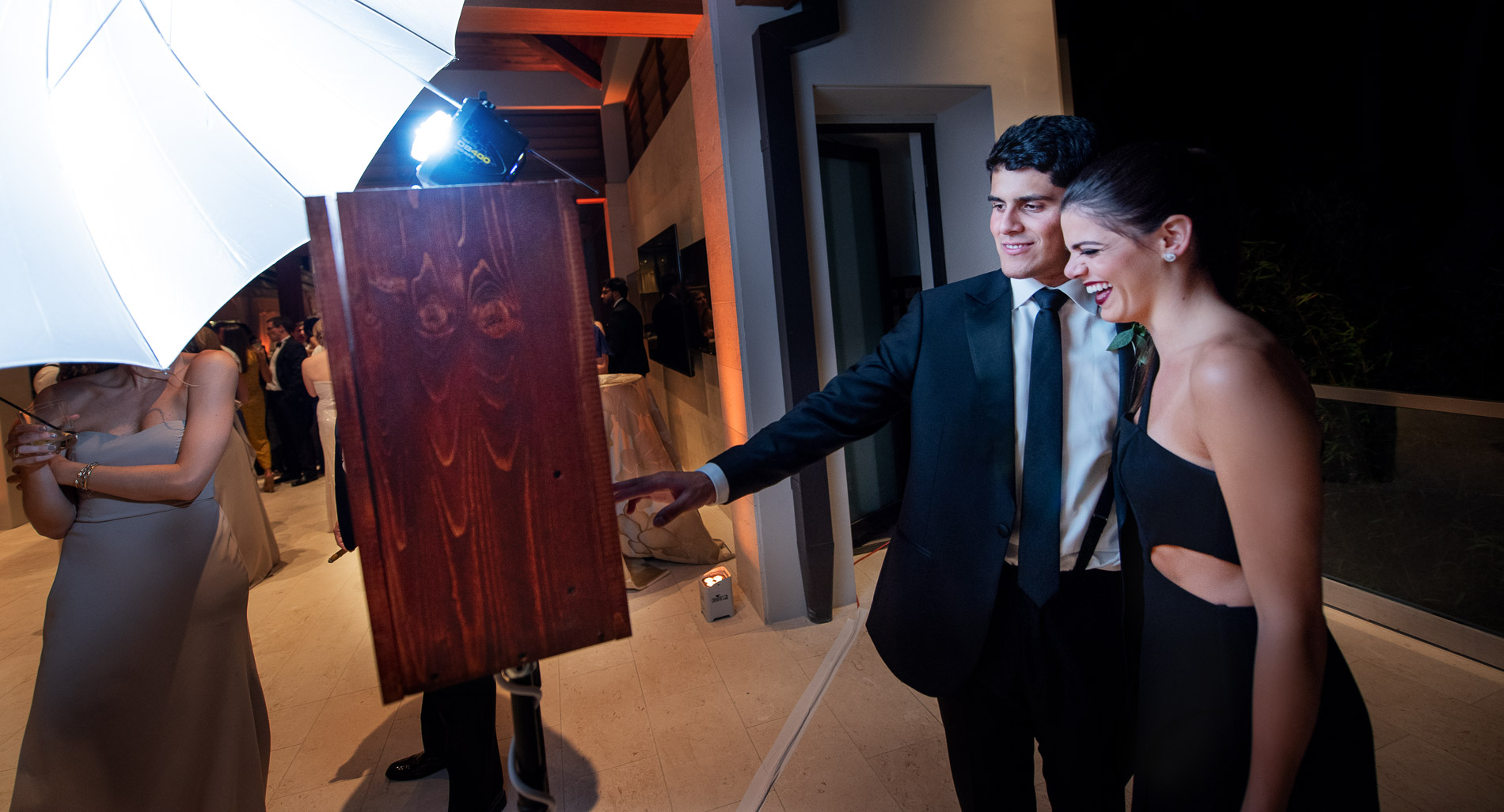 a couple in black uses the photo booth at a wedding