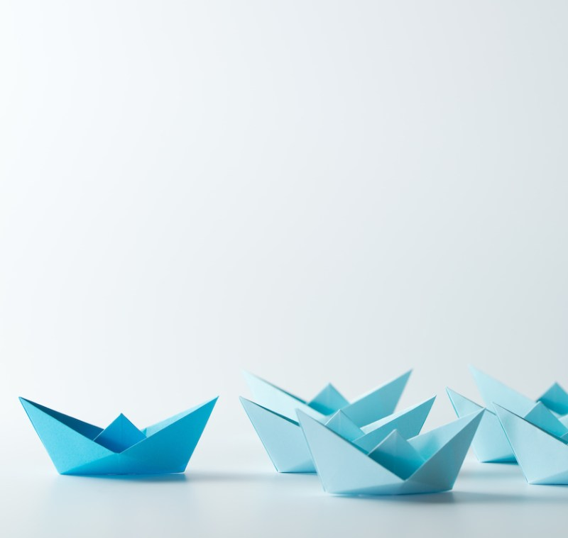 Leadership concept with a dark blue paper ship leading among light blue ships