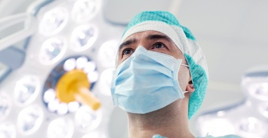 surgery, medicine and people concept - surgeon in mask operating room at hospital