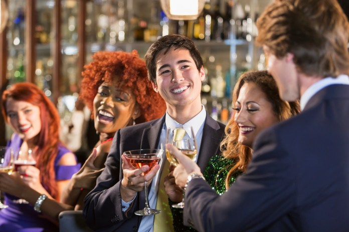 A businessman in a suit with friends in a bar