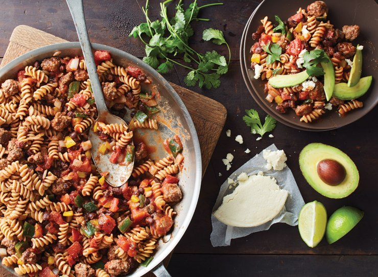 a pan of taco noodles with a spoon, cotija cheese and sliced avocado