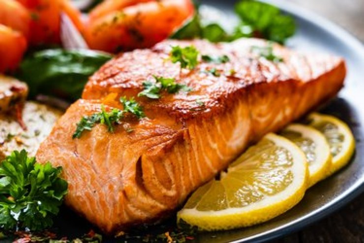 Grilled salmon, fried potatoes and vegetables on a wooden background