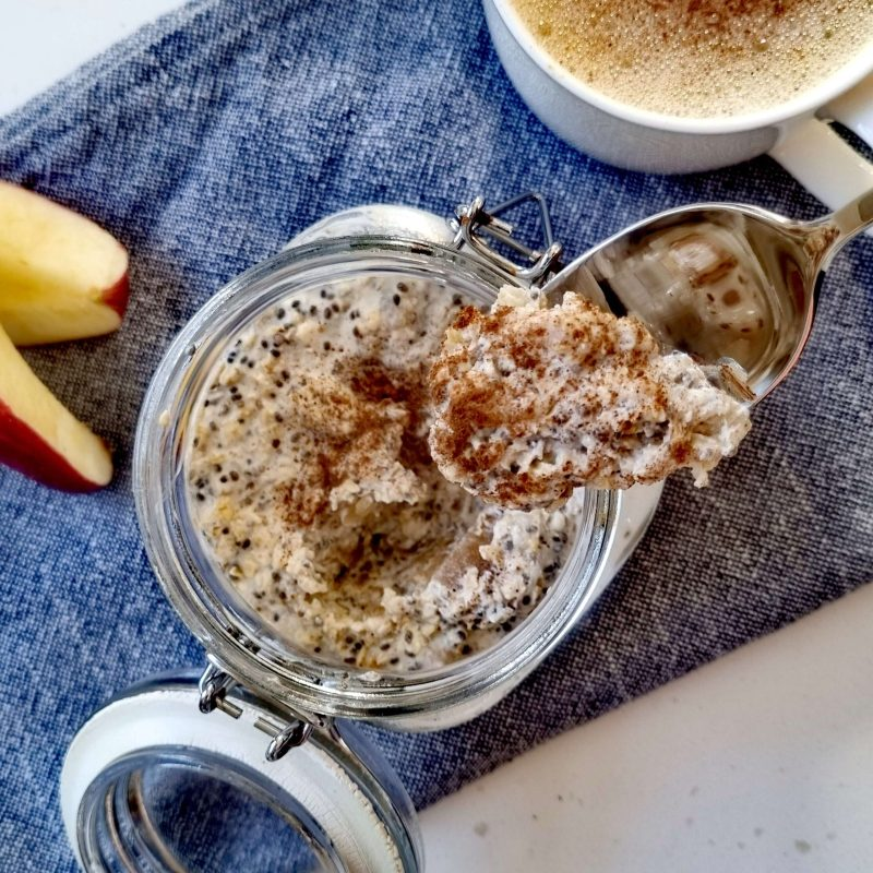 apple overnight oats on a spoon with slices of apple and a cup of coffee