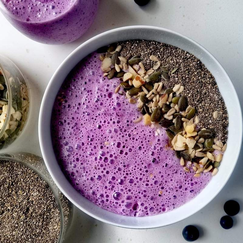 berry protein smoothie bowl with chia seeds , mixed seeds and nuts