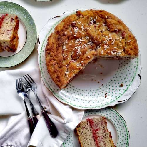 slices of raspberry and coconut cake with the cut cake in the middle on a serving plate