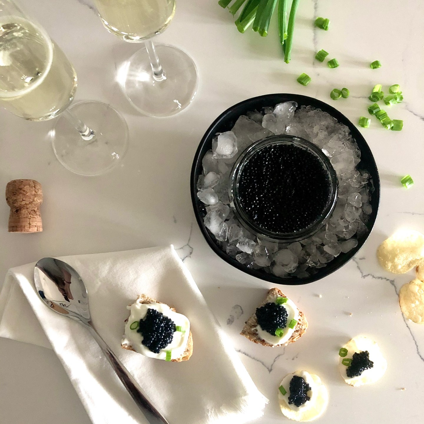 Champagne and vegan caviar on toast points and potato chips with creme fraiche and chives