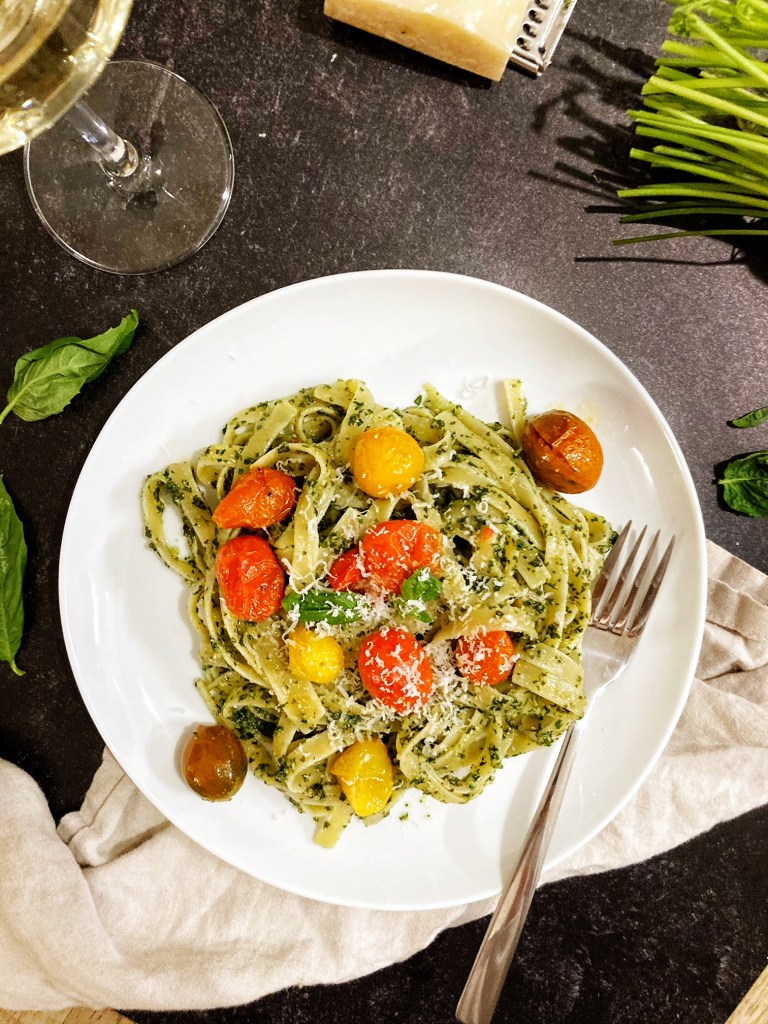 pesto pasta with tomatoes on plate with fork