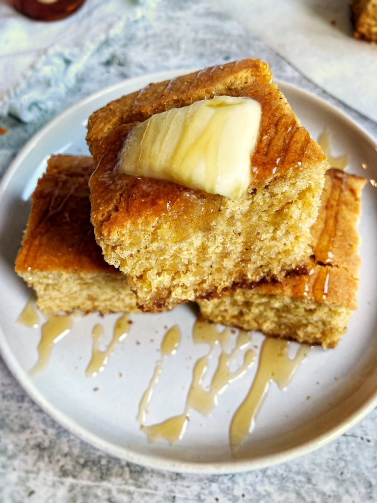 Cornbread squares with melted butter and honey drizzle