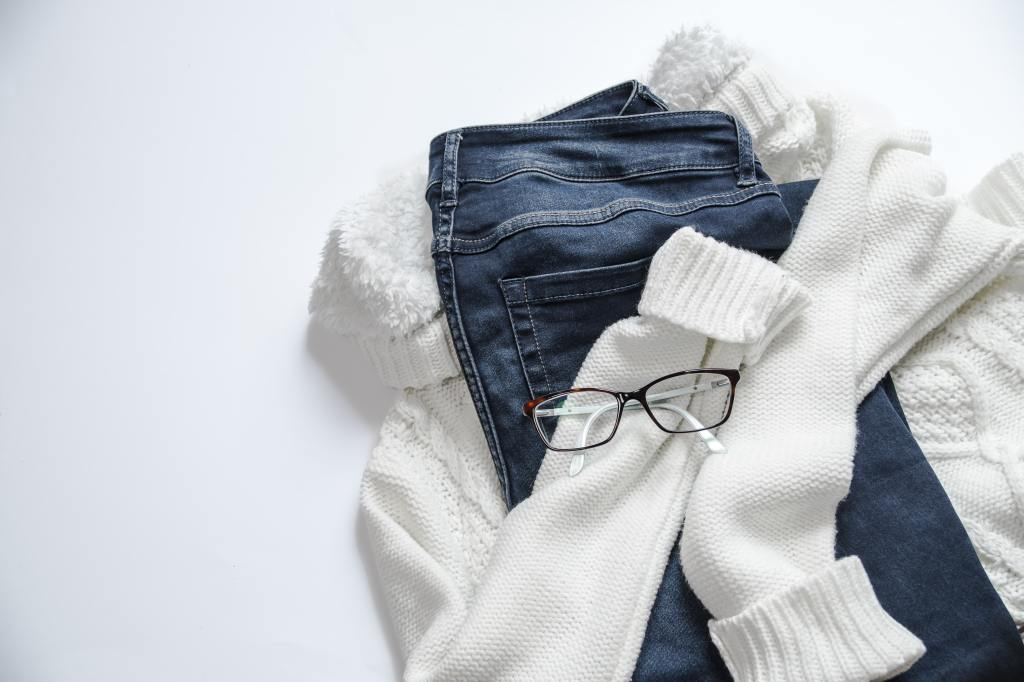 A cozy white sweater hugging a pair of blue jeans with brown glasses on top.