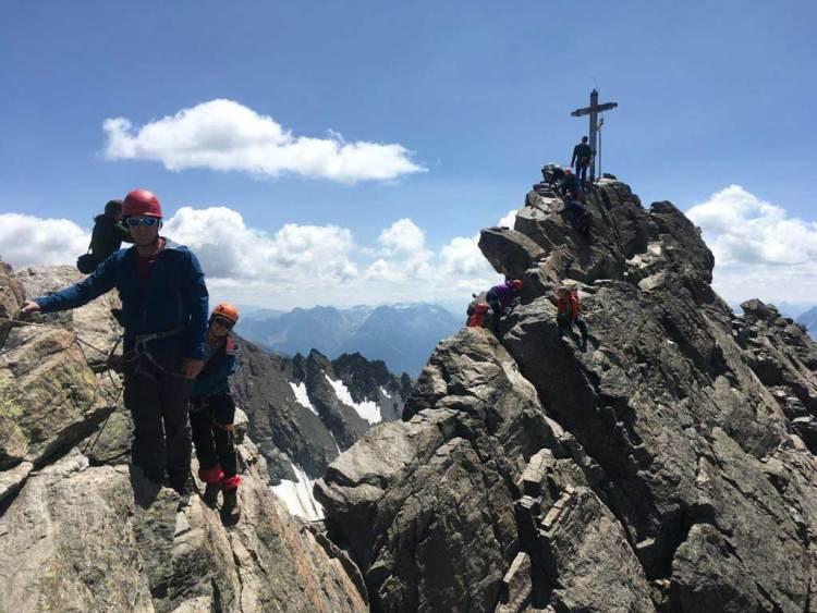 Das Bild zeigt die Dreiländerspitze und den Gipfelgrat mit Gipfelkreuz. Dahinter blauer Himmel mit Wolken.