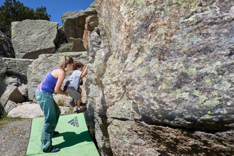 Das Bild zeigt eine Mutter mit Kind beim Bouldern auf einem Gneisblock. Am Boden liegt eine grüne Bouldermatte.