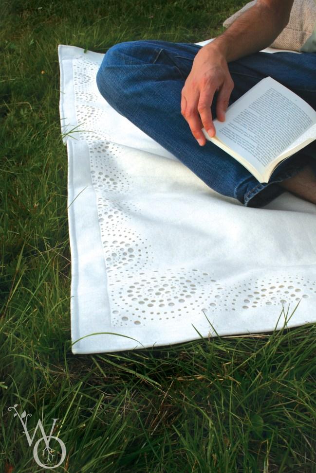 detail of white felt picnic rug in grass.