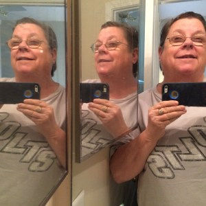 Three faces in the bathroom mirrors.