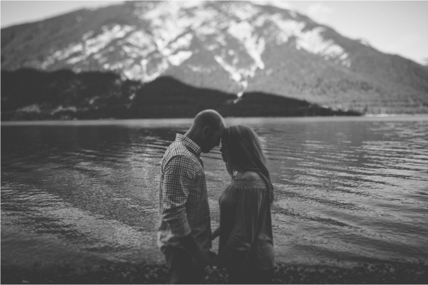 Couple standing face to face in front of a mountain lake in Austria
