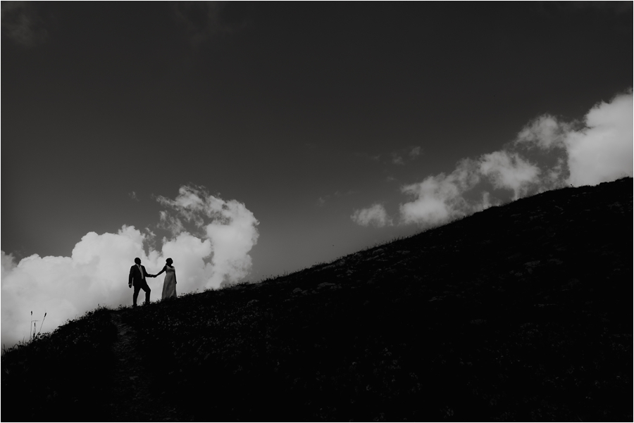 Bride and groom are silhouettes as they walk up a hillside, framed by clouds in Austria Image by Wild Connections Photography