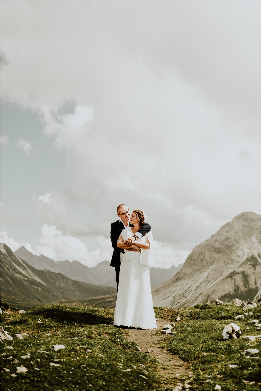 Groom and bride embracing with Lech mountains in the background Image by Wild Connections Photography