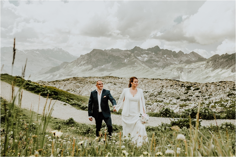 The bride leads the groom through a field of long grass and wildflowers in Lech Austria Image by Wild Connections Photography