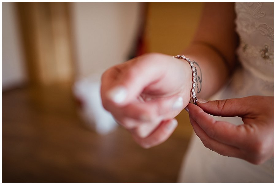 Close up of the hand of bride Michelle as she puts on her swarovski bracelet