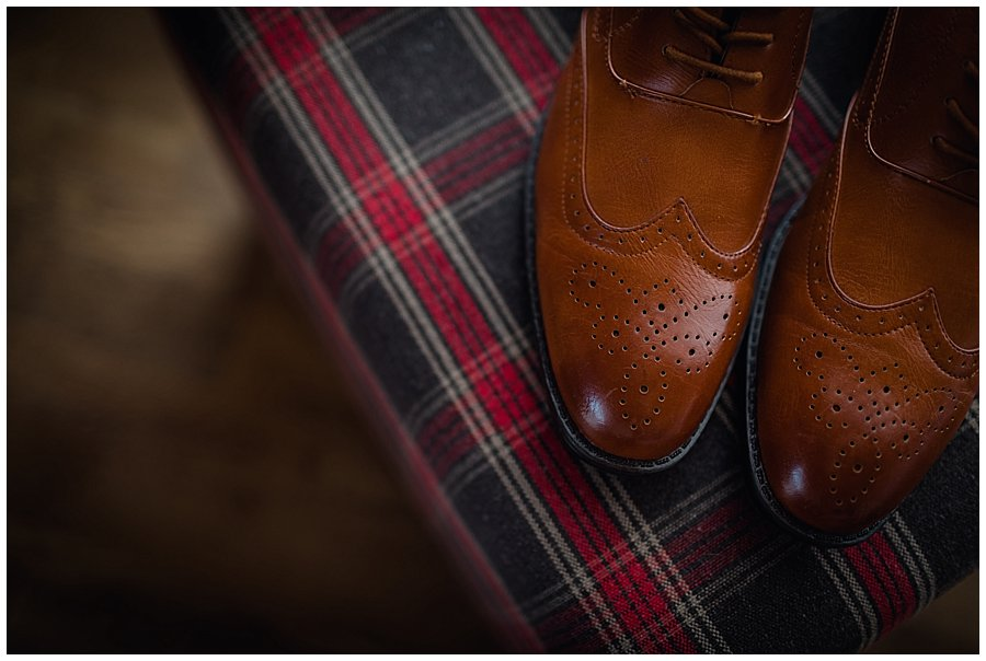 The groom Wayne's brown leather shoes on a tartan fabric stool