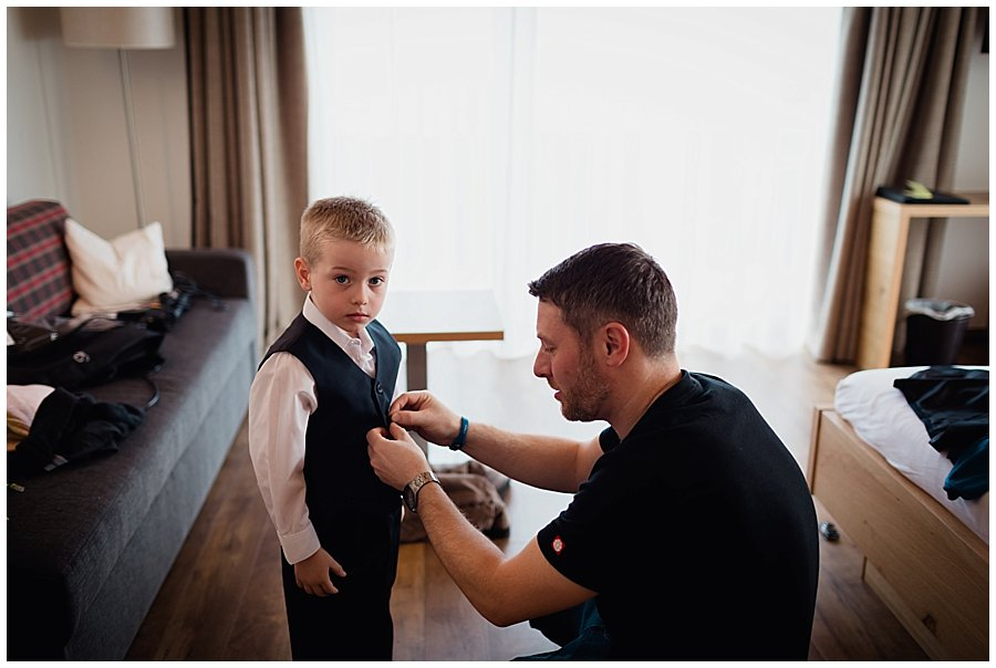 The groom Wayne helps his son getting dressed for the wedding