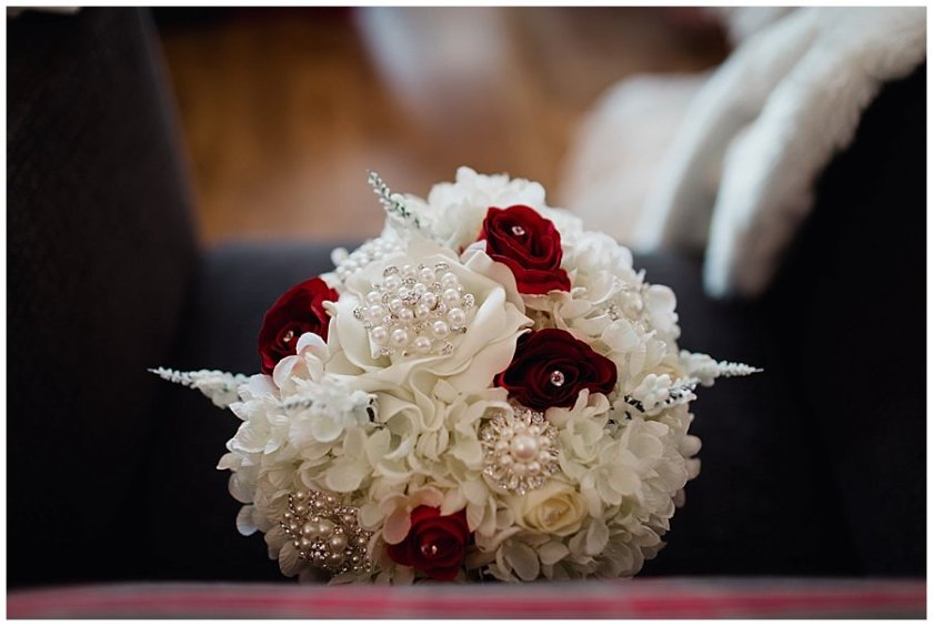 An artificial flower bouquet in red and white with lots of brooches
