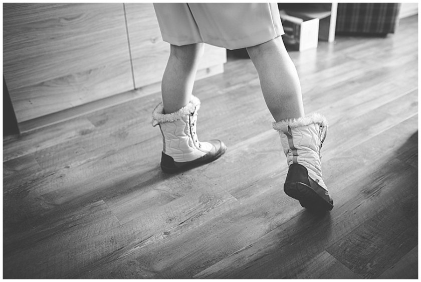 The mother of the bride models her snow boots for the wedding