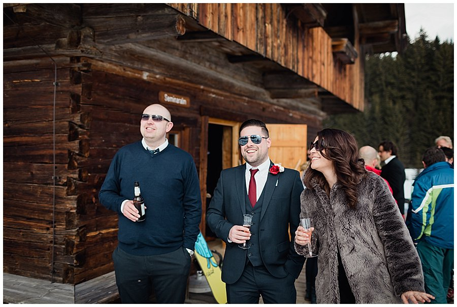 Wedding guests stand outside the mountain cabin with drinks and look out towards the mountains
