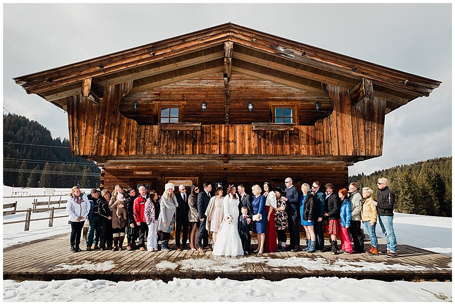 A group picture of the whole wedding party outside the seminaralm mountain hut in Brixen im Thale