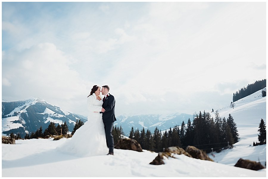 Wayne and Michelle stand facing each other in the snow with snow covered mountains in the background