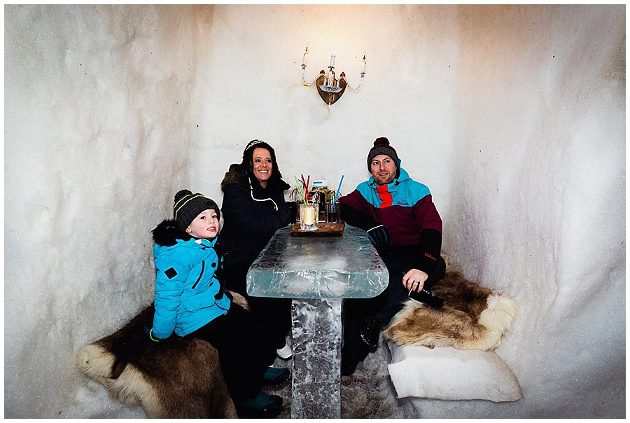 Wayne, Michelle and Ethan enjoy a drink in an ice booth sitting at an ice table in the igloo