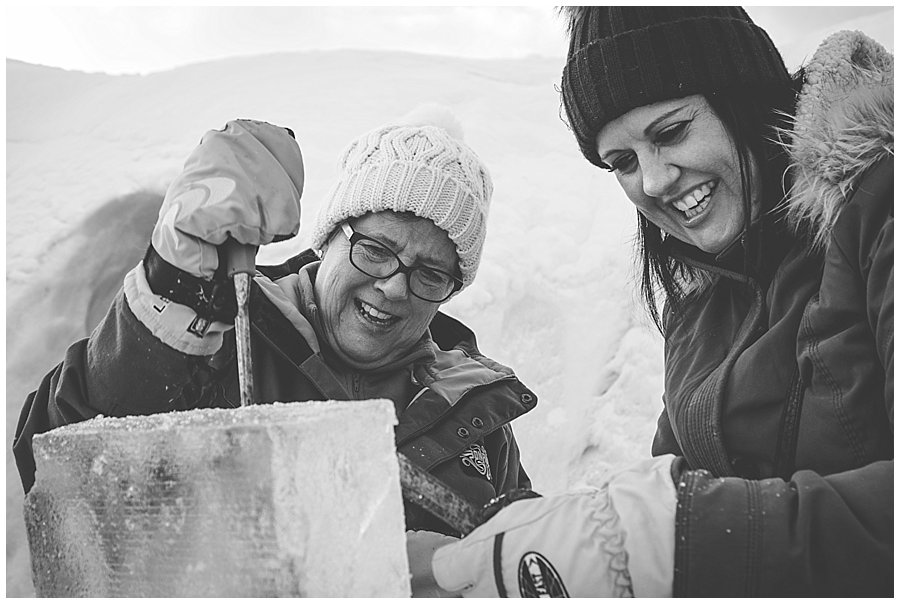 Two ladies laughing as they chip away at their ice block