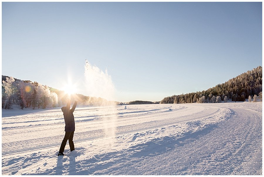 A woman throwing snow up in the air on a frozen lake in Levi Finland