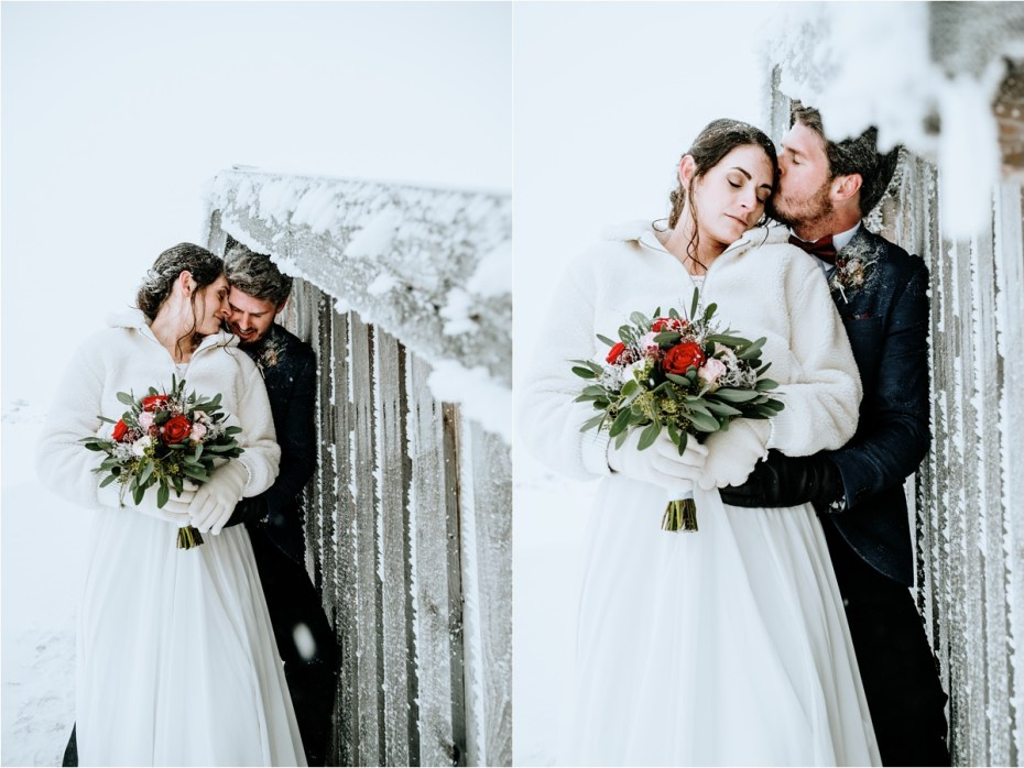 Bride and groom take shelter from the wind behind a wooden mountain hut. Photos by Wild Connections Photography