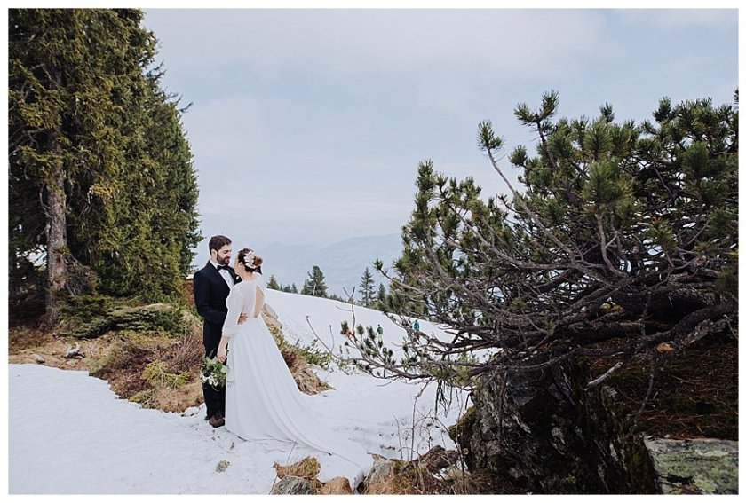 Bride and groom standing in the snow facing each other