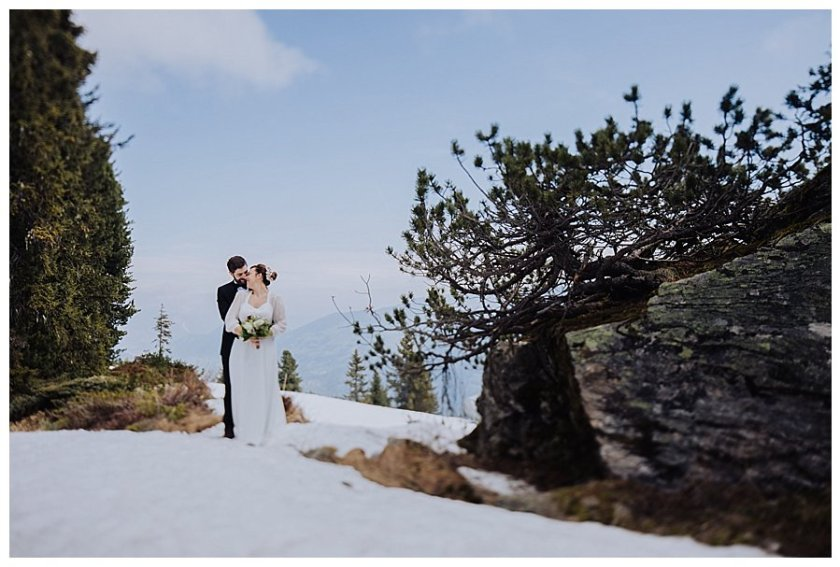 Wide shot of Susana and Tiago looking at each other whilst standing in the snow on a mountain in Austria