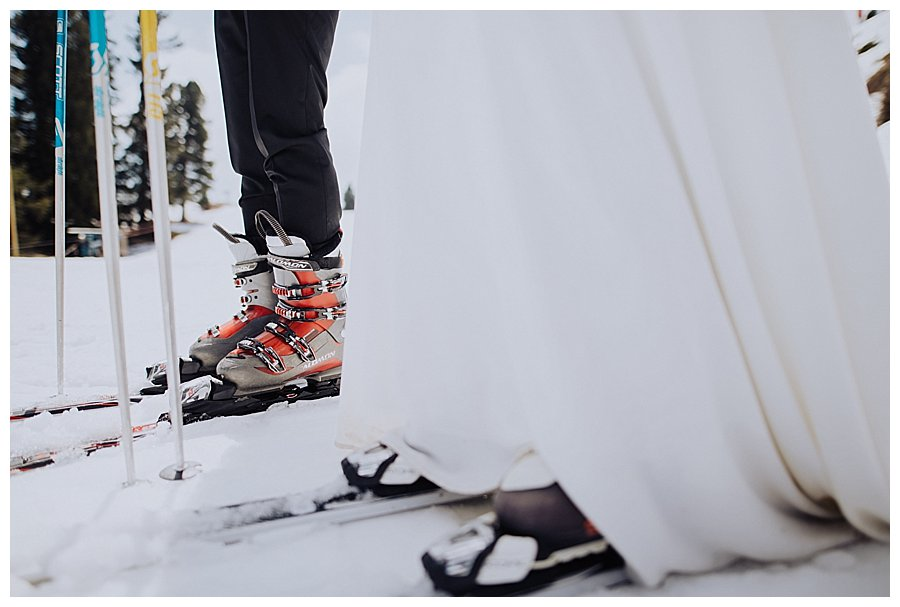 Close up of the bride and groom wearing ski boots and skis