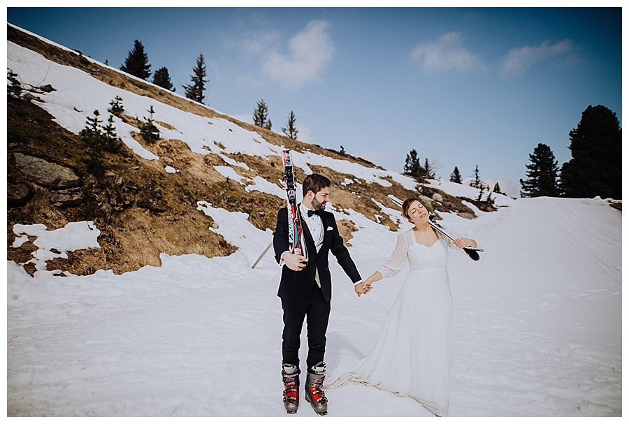 Bride and groom walking along in the snow carrying their skis