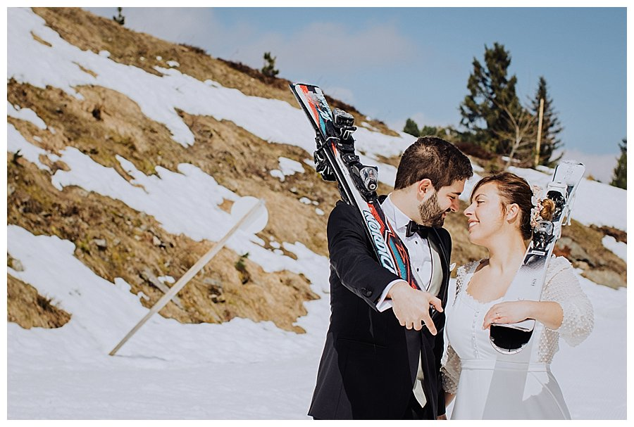 Bride and groom leaning in for a kiss whilst carrying skis