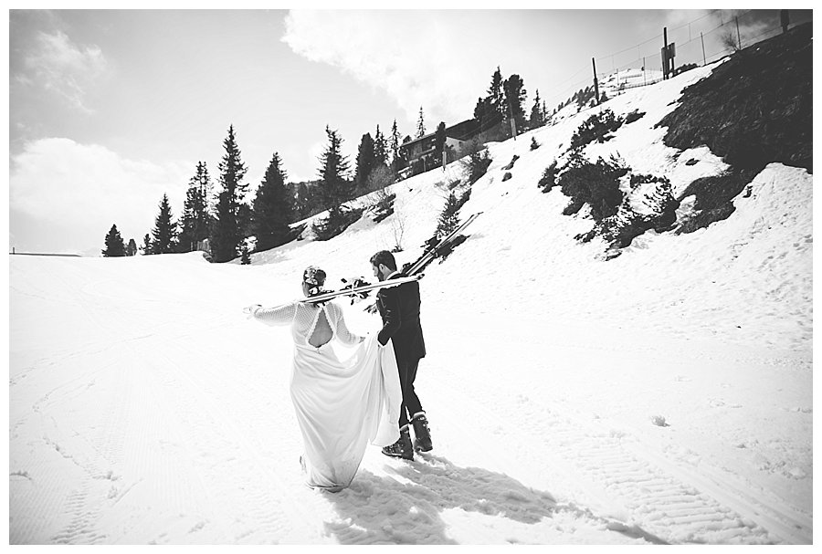 Groom holding the bride's dress as they walk up a ski slope during a honeymoon trash the dress shoot in Austria by Wild Connections Photography