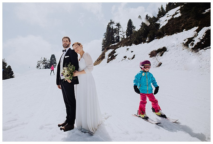 A small child skis past the bride and groom who are standing on the ski slope during a honeymoon trash the dress shoot in Austria by Wild Connections Photography