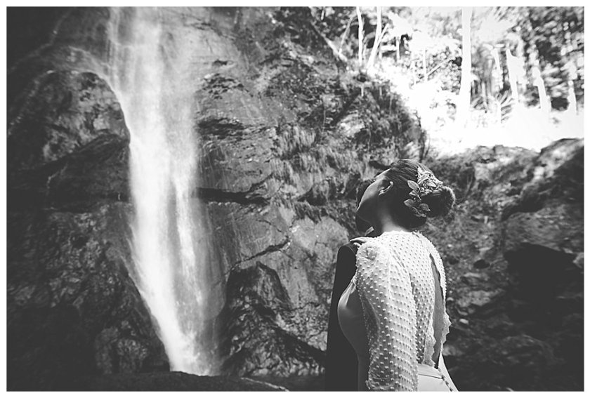 A picture from behind the bride as she looks up at the waterfall