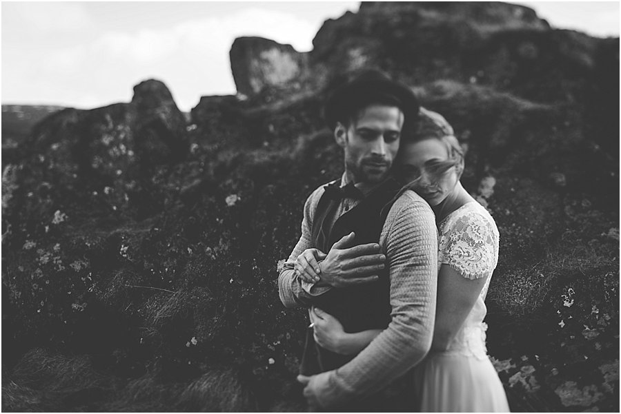 Thingvellir wedding Bride and groom embracing with rocks behind them. Bride's hair is blowing across her face by Wild Connections Photography
